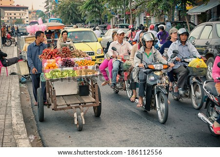 PHNOM PENH, CAMBODIA - 29 DEC 2013: Heavy traffic through the city streets in the evening. The main part of transport - motorcycles - stock photo