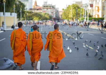 PHNOM PENH, CAMBODIA - DECEMBER16: Unidentified buddhist monks walk along the road on December 16, 2011 in Phnom Penh, Cambodia. 95 percent of cambodian population practice Theravada Buddhism.  - stock photo