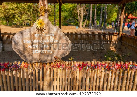 PHNOM PENH, CAMBODIA - FEBRUARY 28, 2014: A fenced enclosure and sign mark a mass grave at the Choeung Ek Genocidal Center (the Killing Fields). The center memorializes the thousands executed here. - stock photo