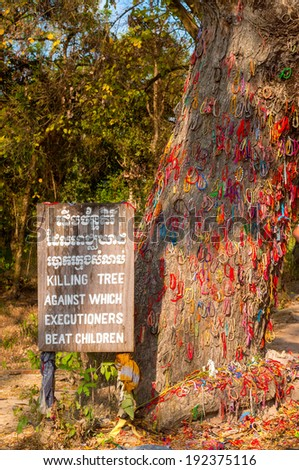 PHNOM PENH, CAMBODIA - FEBRUARY 28, 2014: A tree used for killing children is festooned with ringlets at the Choeung Ek Genocidal Center (Killing Fields). The park honors the thousands who died here. - stock photo