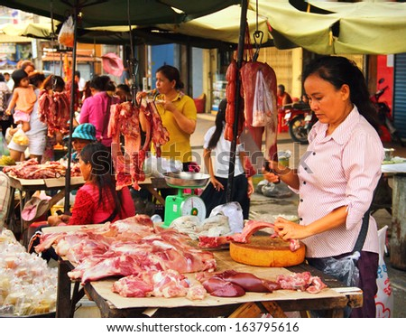 PHNOM PENH/CAMBODIA - MAY 09. Unidentified khmer woman cuts and sales a meat  on may 09, 2013 in Pnom Penh central market, Cambodia, South East Asia