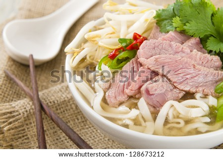Pho Bo - Vietnamese fresh rice noodle soup with beef, herbs and chili. Vietnam's national dish. - stock photo