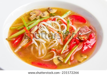 Pho bo, Vietnamese soup with with rice noodles, beef and mushrooms in white plate - stock photo