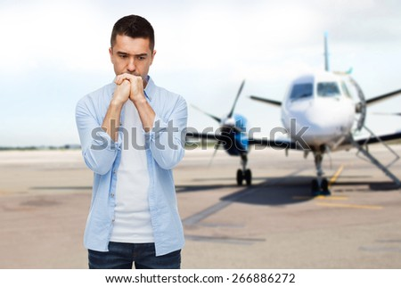 phobia, fear, sorrow and people concept - unhappy man thinking over airplane on runway background - stock photo