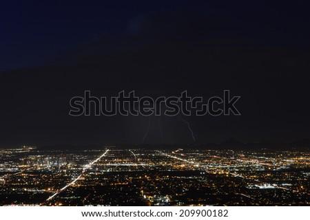 Phoenix city lights at dusk with three lightning strikes - stock photo