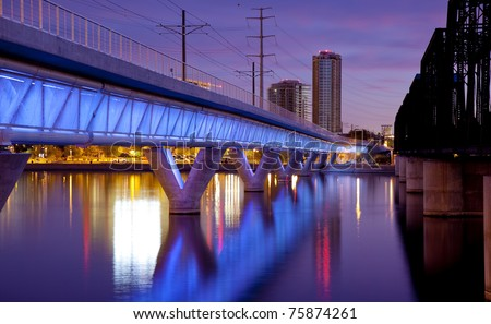 Phoenix Metro light rail bridge across the Salt River in Tempe Arizona photographed at sunset. - stock photo