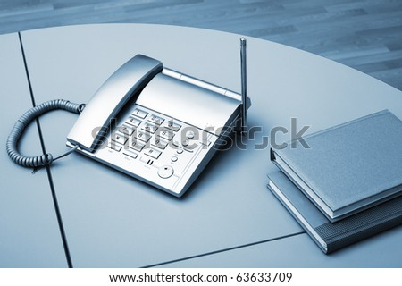 Phone and two books on a table at office - stock photo