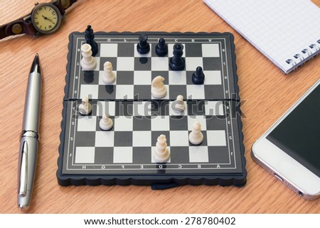 phone background chess clock and notebook on the table - stock photo