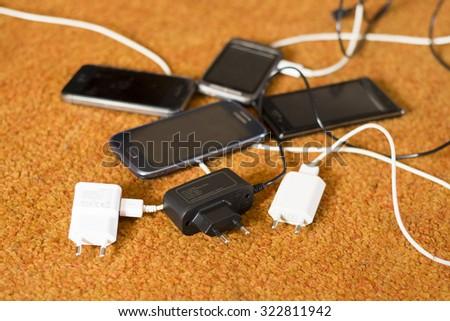 Phone Chargers on the orange carpet floor - stock photo