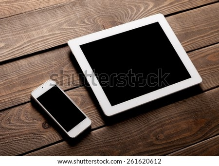 Phone. Digital tablet computer and white smart phone with isolated screens on old wooden desk. - stock photo