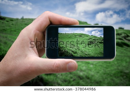 phone in hand man (photographing the landscape) photos from your phone, Self, photographing on the phone, the man photographs the mountain landscape on the phone (smartphone) side view