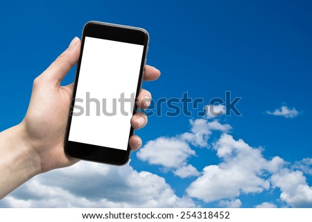 phone in the hand with a blank screen on a background of the sky - stock photo