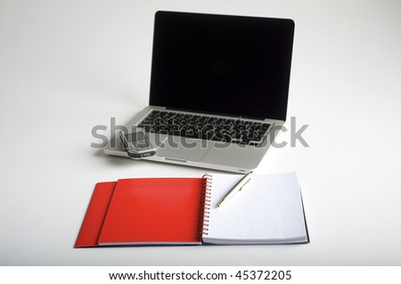 Phone, laptop and empty notebook on the desk - stock photo