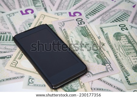 Phone on a background of money. Concept. - stock photo