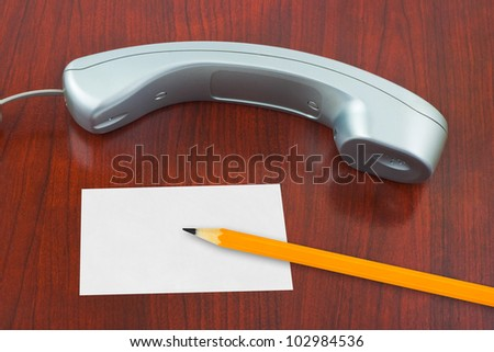 Phone, paper card and pencil on wooden table - stock photo