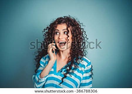Phone talk. Closeup portrait headshot beautiful woman talking on mobile phone isolated blue wall background. Curly hair girl striped shirt Positive human emotion face expression reaction body language - stock photo