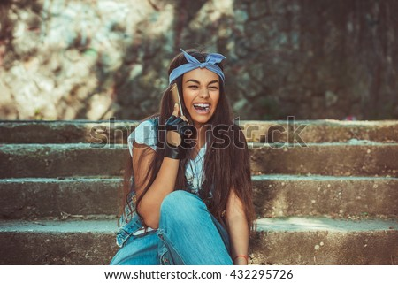 Phone talk. Closeup portrait headshot beautiful woman talking on mobile phone laughing looking away sitting on stairs green grey wall background. Brunette dark head hip hop girl Positive human emotion - stock photo
