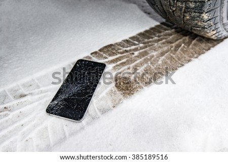 Phone with broken screen on snow in car trail. Glass covered with snow flakes. Device run over by wheel. - stock photo