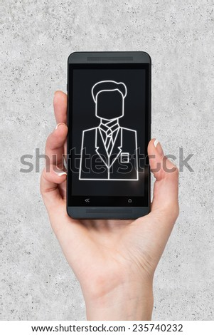 phone with businessman icon  in hand on gray background - stock photo