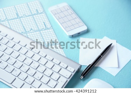 Phone with cardiogram on screen on doctor workplace - stock photo