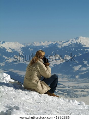 Phoning with a mobile phone  watching Innsbruck, Austria. - stock photo
