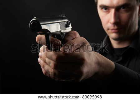 photo a young man drawing a gun in self defense studio shoot - stock photo