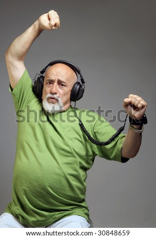 photo af a senior with headphones listening music - stock photo