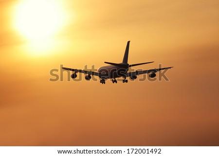 Photo aircraft flying at sunset - stock photo