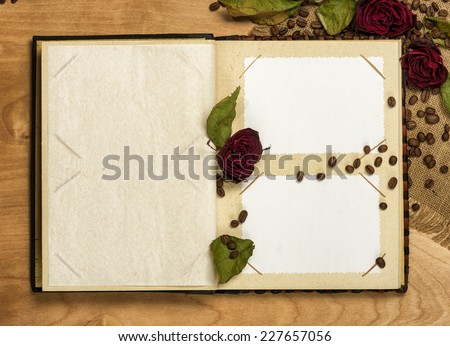 photo album and dry red roses on coffee seeds - stock photo