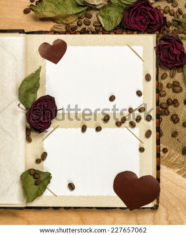 photo album and dry red roses on coffee seeds