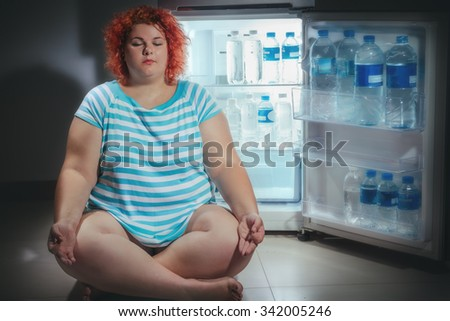 Photo at night of Overweight woman opening refrigerator and sits in pose of lotus and meditates. - stock photo