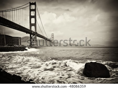 photo beautiful b&w golden gate bridge in san francisco California . black and white golden gate bridge in san francisco with water crashing into the pier and rocks.