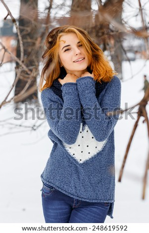 Photo beautiful woman in winter park. The park is a lot of snow. - stock photo