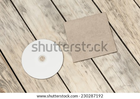 Photo blank. Compact disk and cover on a old wooden texture - stock photo