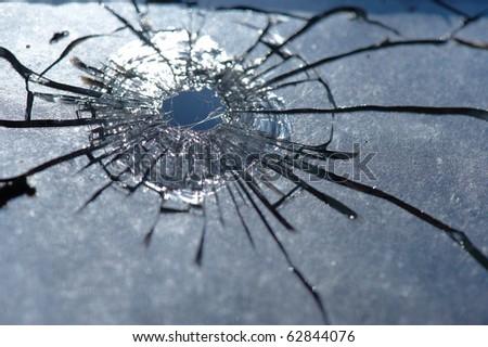 photo broken window looks like a bullet hole - stock photo