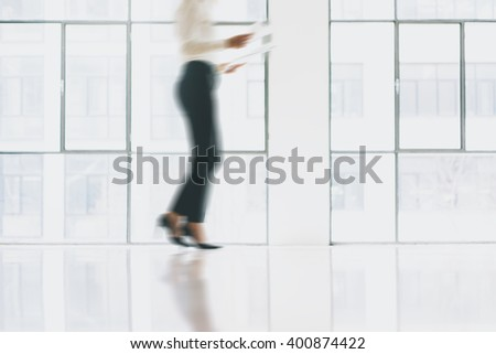 Photo business woman in motion, wearing modern suit. Open space loft office. Holding papers hands. Analyze plans, meeting, panoramic windows background. Motion blur. Horizontal mockup.