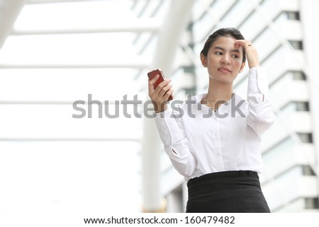 Photo business woman thinking something with her mobile phone,Serious - stock photo