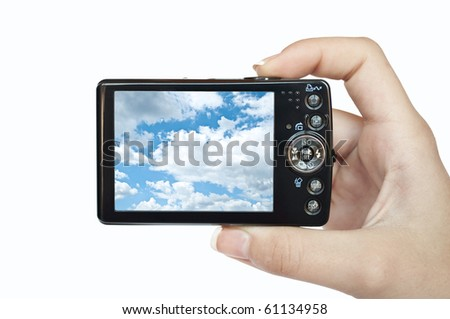 Photo camera in hand isolated on white background with picture of sky - stock photo