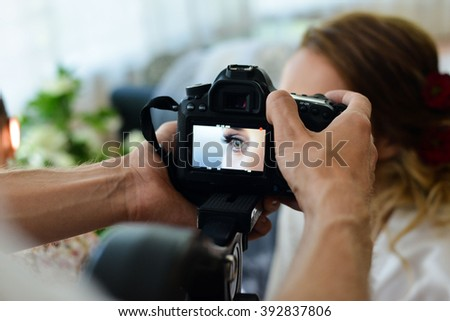 Photo camera in hand shoots a wedding every day - stock photo