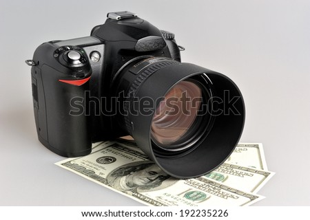 Photo camera with dollars on gray background - stock photo