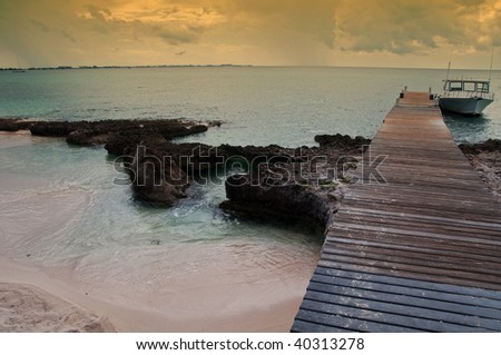 photo capture of a boat on a tropical island beach - stock photo