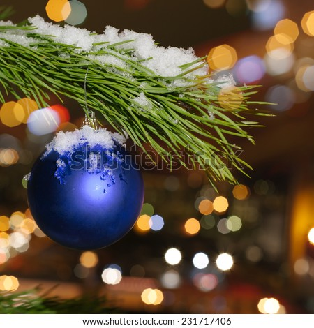 Photo Christmas ball on a Christmas tree branch on a background of the night city lights - stock photo