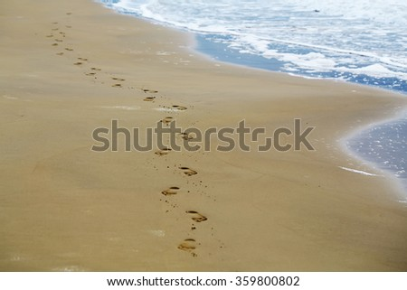 Photo closeup of bare human feet prints on beautiful beige beach sea marine grained sand against blue waves running on seashore on seascape background, square picture - stock photo