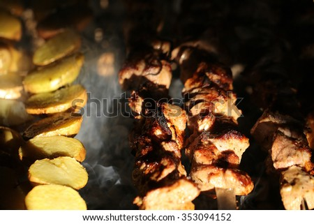 Photo closeup of delicious hot potatoes and meat skewers cooked on grill charbroiled barbecue on brazier on blurred smoky background, horizontal picture  - stock photo
