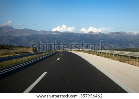 Photo closeup of modern new asphalt highway twisting lane crooked alignment of road wheeling roadway broadway through passage against mountain scene background, horizontal picture