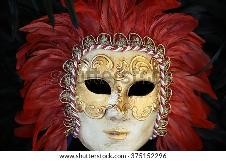 Photo closeup of one distinctive Venetian carnival mask with beautiful decoration of natural red feathers classic accessory for sale outdoor on wall on black plume background, horizontal picture