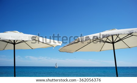 Photo closeup of two white beach umbrellas for sun protection in line at seashore silhouetted against bright blue sky and sea on seascape background, horizontal picture - stock photo