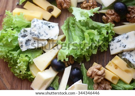 Photo closeup of various types of gourmet cheese slices triangles with mold green salad black olives and walnuts on wooden platter background, horizontal picture - stock photo