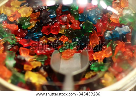 Photo closeup selection of variety mixed colorful gummy jelly bears gumdrops candies sweeties in plastic bowl with scoop for pick and sale on gum confectionery background, horizontal picture - stock photo