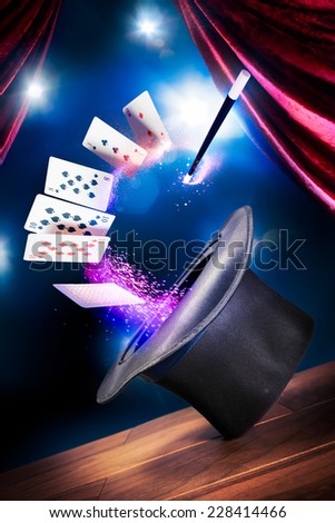 photo composite of a magic hat with cards and a wand on a stage  - stock photo
